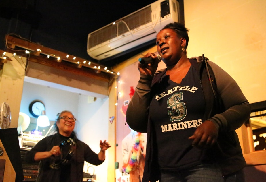 caption: Hoden Babu sings karaoke as host Karen Sakata backs her up on the tambourine at Bush Garden