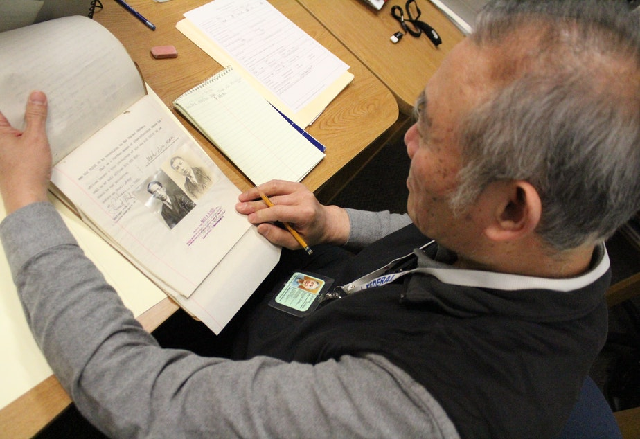 caption: Volunteer Hao Jang Chang looks through a file from the era of the Chinese Exclusion Act at the National Archives in Seattle.