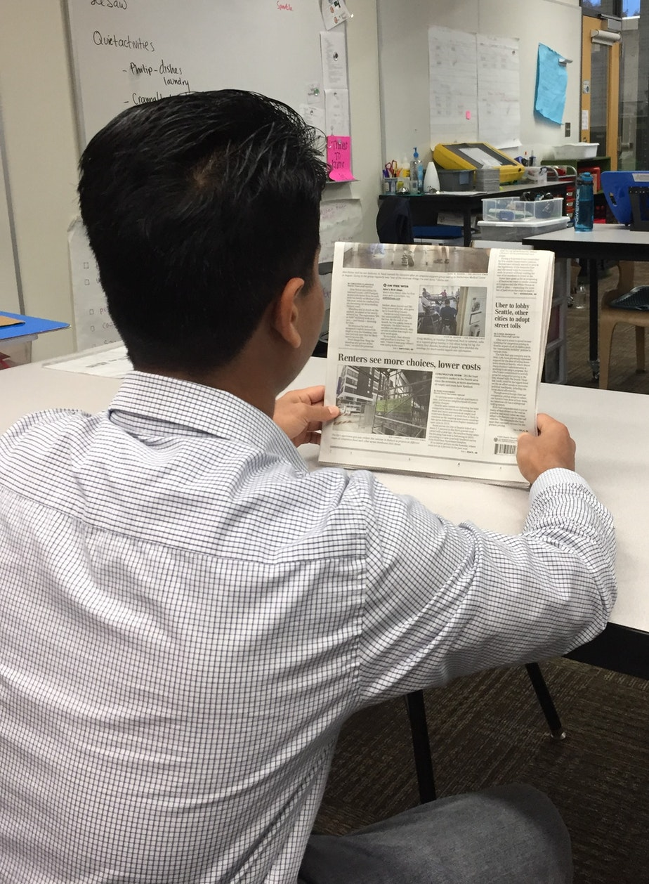 Mohamad Imran reads the newspaper in classroom on Mercer Island.