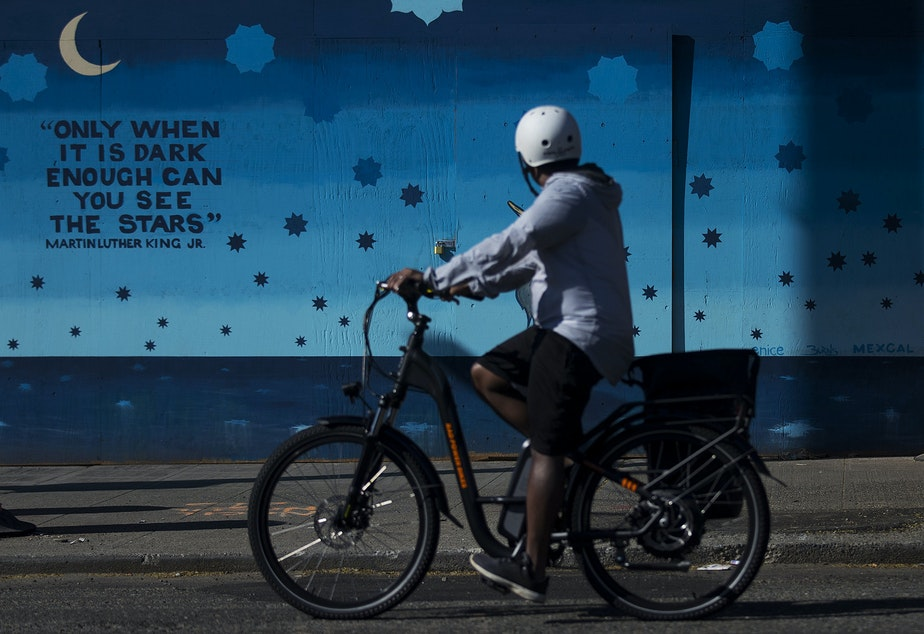 "caption: A cyclist looks toward a mural painted by Scott McCall, covering the boarded up facade of Pho Big Bowl, along NW Market Street on Monday, April 20, 2020, in Seattle. The quote from Martin Luther King Jr. reads, ""only when it is dark enough can you see the stars."""
