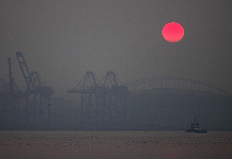 caption: The sun rises over Seattle as a massive plume of smoke from wildfires burning in California and Oregon makes it's way into the area on Friday, September 11, 2020, in Seattle.