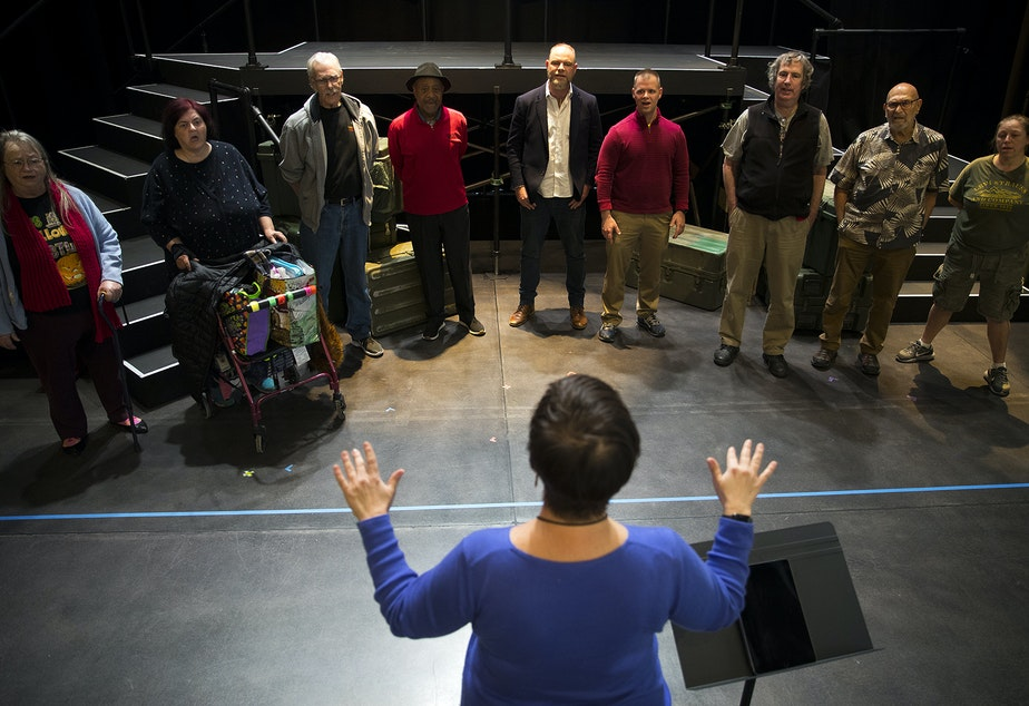 caption: Seattle Opera teaching artist Liz Frazer conducts the veterans choir during a final presentation rehearsal on Thursday, October 31, 2019, at Seattle Opera on Mercer Street in Seattle.