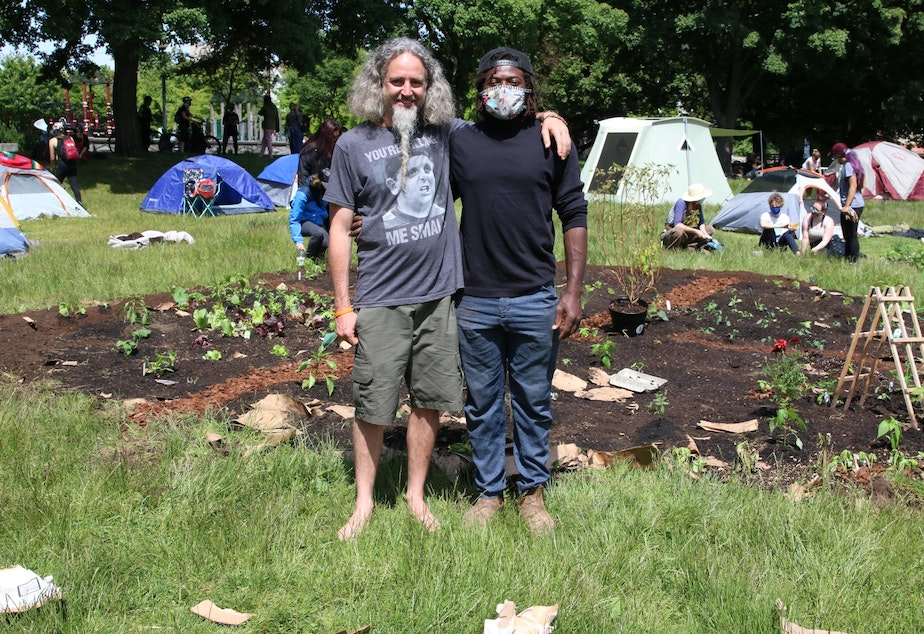 caption: Marcus Henderson (R) came down with a shovel on his bike and started digging. Others donated compost, plants. Water comes from the reservoir fountain behind them.
