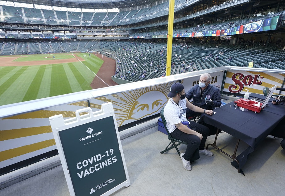 caption: Seattle Mariners fan Nick Pham, left, gets the Johnson & Johnson COVID-19 vaccine shot from Bill Allemann, right, of the Seattle Fire Dept., Tuesday, May 4, 2021, during a clinic held at T-Mobile Park before a baseball game between the Mariners and the Baltimore Orioles in Seattle. The Mariners will be offering free COVID-19 vaccines to eligible fans at three locations in the ballpark during upcoming home games.