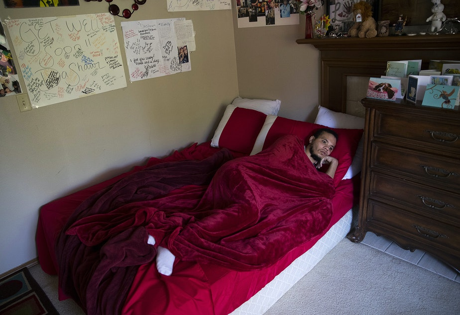 caption: DaShawn Horne rests in his newly converted bedroom on the first floor shortly after arriving home from spending 103 days at hospital, on Thursday, May 3, 2018, at their home in Auburn.