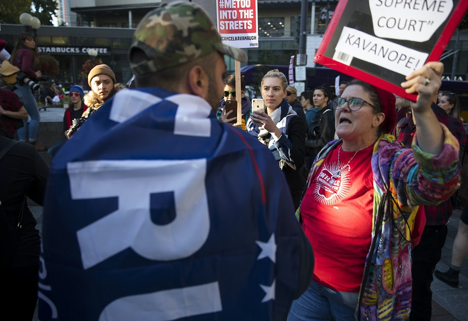Kathryn Lewandowsky, right, and Armen, left, a member of the UW College Republicans, speak during the 'Cancel Kavanaugh - We Believe Survivors' march and rally on Thursday, October 4, 2018, at Westlake Park in Seattle.