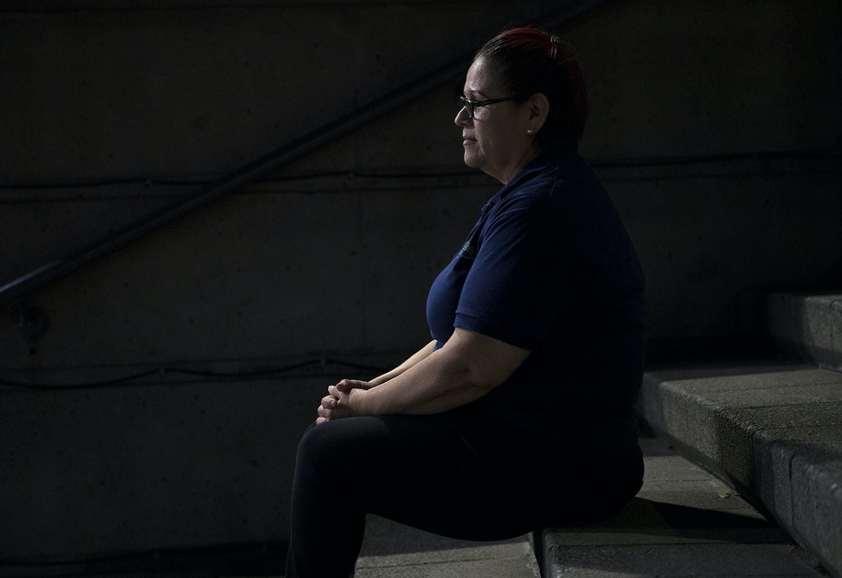 caption: A woman who works the overnight janitorial shift sits for a portrait at 2:13 a.m. on Thursday, June 13, 2019, in downtown Seattle.