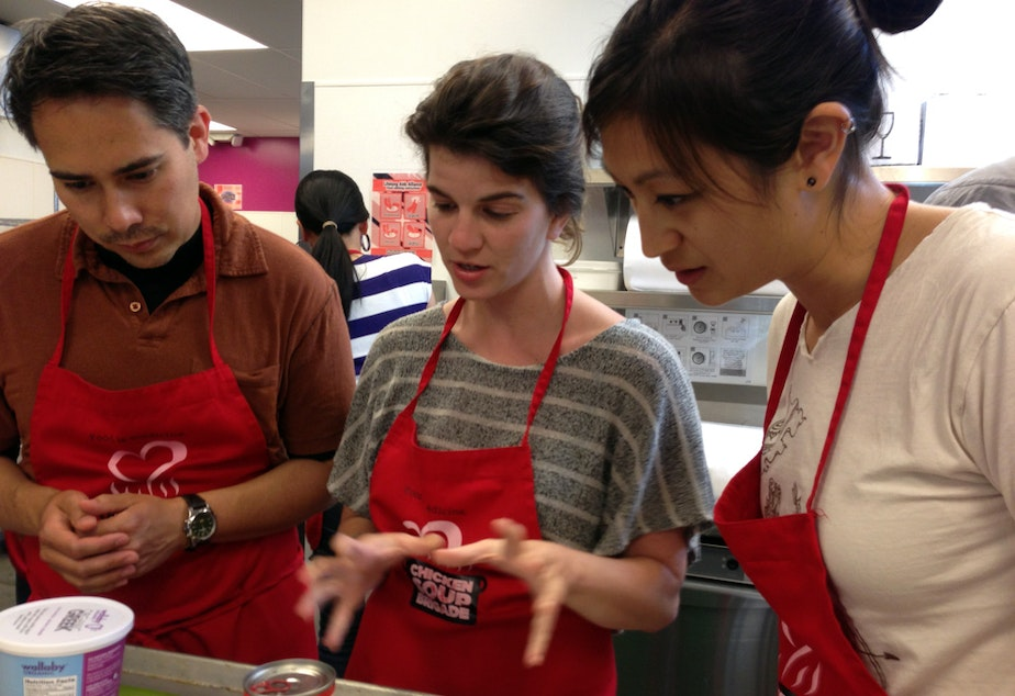 Medical residents Bryn Chowchuvech, Bari Laskow  and Tiffany Ho discuss strategy for making their spaghetti dish.