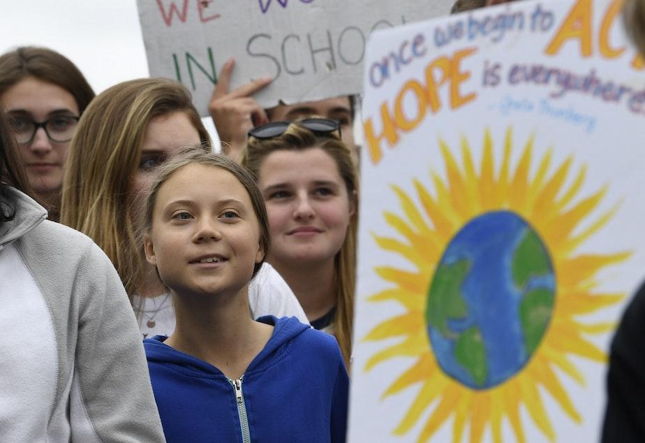 caption: Swedish youth climate activist Greta Thunberg, center, marches with other young climate activists for a climate strike outside the White House in Washington, Friday, Sept. 13, 2019.