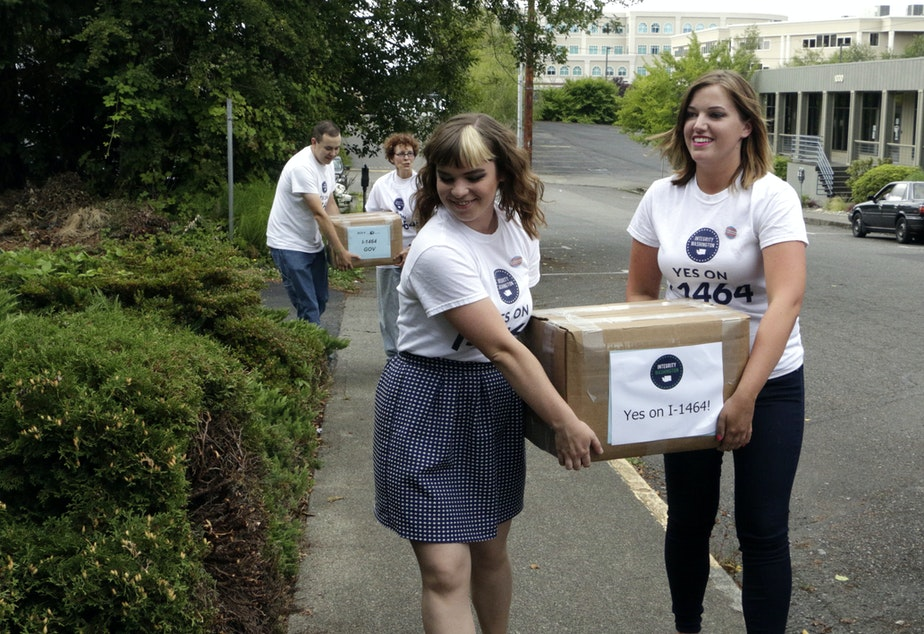 caption: File photo: Supporters of a proposed campaign finance reform ballot initiative carry boxes of signed petitions to turn in, on July 8, 2016, in Olympia.