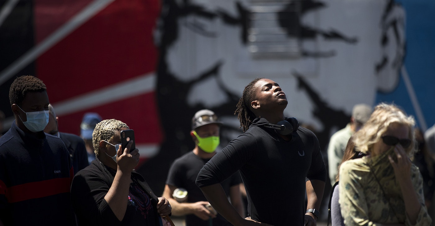 caption: Hanz Jouissance, center, stands in front of a mural of Dr. Martin Luther King Jr. while attending a vigil to recognize the senseless killing of African American men and women outside of the First African Methodist Episcopal Church on Monday, June 1, 2020, in Seattle.