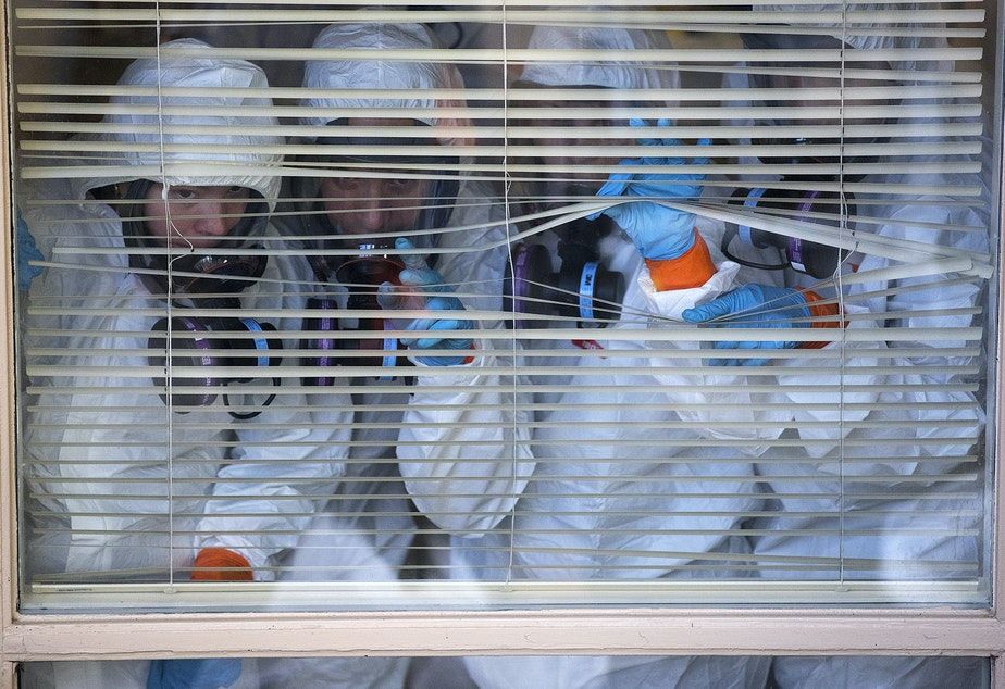 caption: Members of a Servpro cleaning crew look out of a window before taking a break from cleaning the interior of the Life Care Center of Kirkland, the long-term care facility at the epicenter of the coronavirus outbreak in Washington state, on Wednesday, March 11, 2020, in Kirkland.