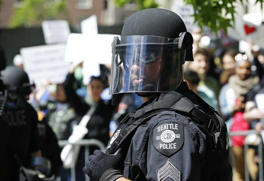 A Seattle Police officer watches counter-protesters as they stand behind barricades across the street from an anti-Islamic law rally Saturday, June 10, 2017, in Seattle.