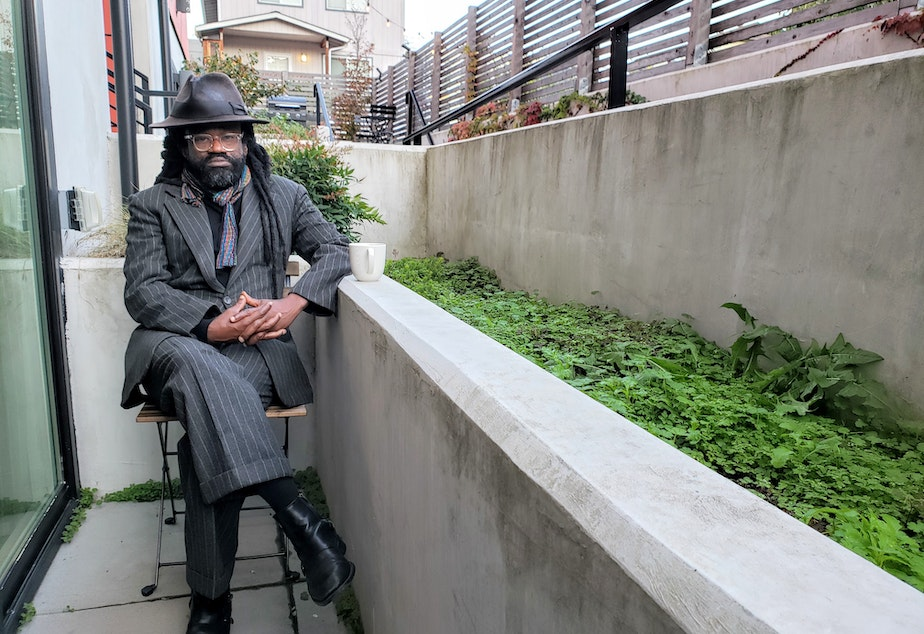 caption: Reverend Osagyefo Sekou sits outside of his Seattle apartment days before he leads a non-violent, civil disobedience training. Thursday, October 29, 2020.