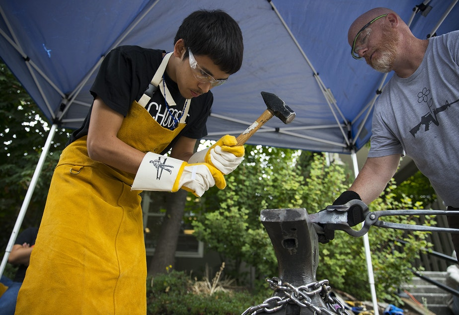 Nick Oyoghok, 17, forges the barrel of a 22-gauge shotgun into a mattock gardening tool with the help of Brian Hewitt, right, on Tuesday, July 23, 2019, at Choose 180 in Burien.