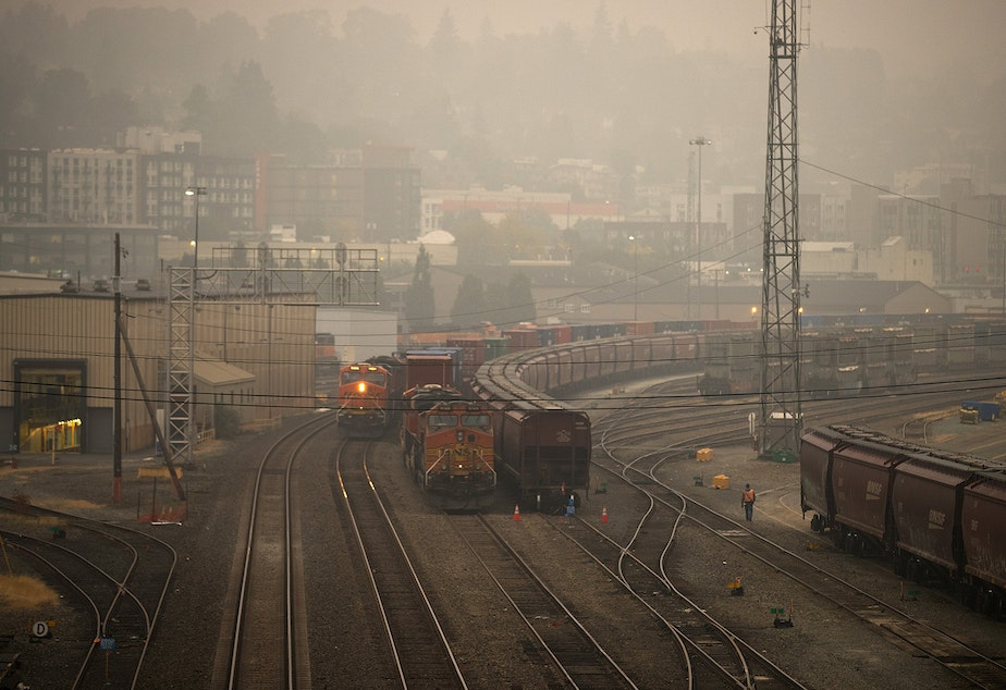 caption: Air quality in Seattle has turned hazardous according to the state Department of Ecology, as wildfire smoke from California and Oregon continues to settle in the area. Here, a worker walks through Balmer Yard on Saturday, September 12, 2020, in Seattle.