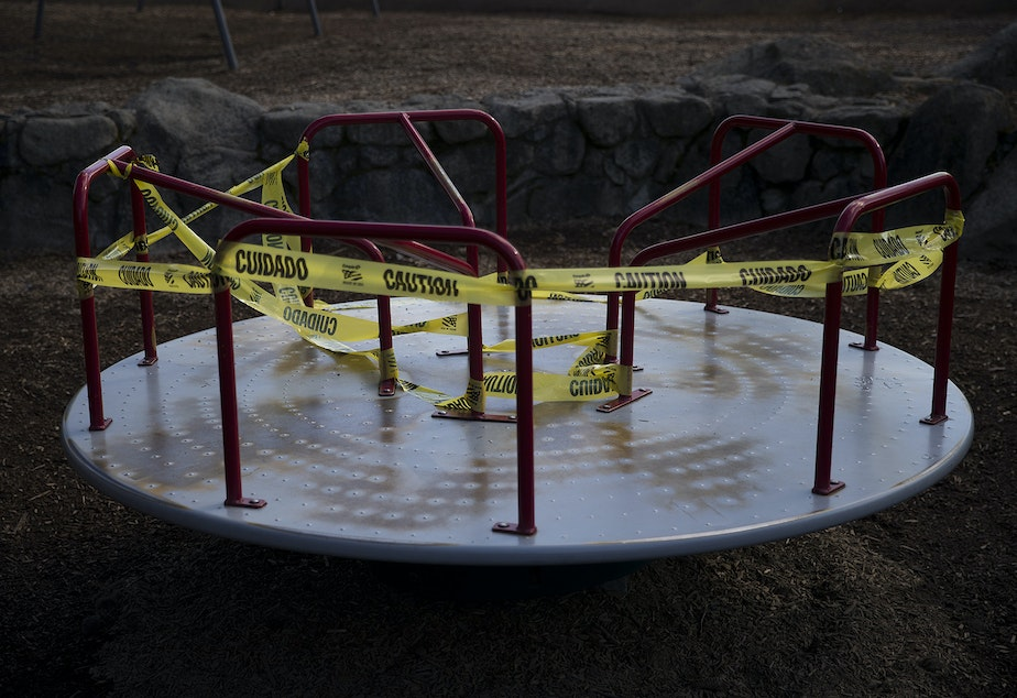 caption: A portion of a playground is off limits and surrounded by caution taped on Wednesday, March 25, 2020, at Seward Park in Seattle.