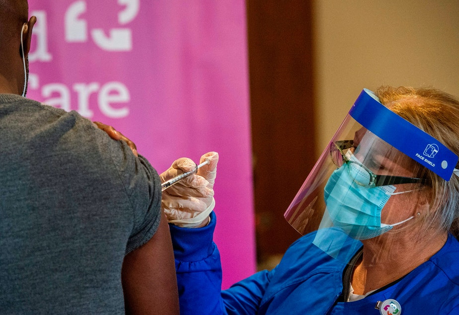 caption: Nurse Keith Grant got his second dose of Pfizer's COVID-19 vaccine on schedule from RN Valerie Massaro in January at the Hartford Convention Center — 21 days after his first immunization.