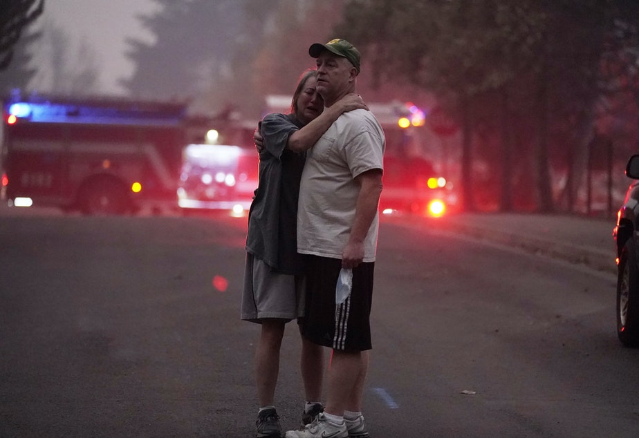 caption: A couple embrace Thursday while touring an area devastated by the Almeda Fire in Phoenix, Ore.