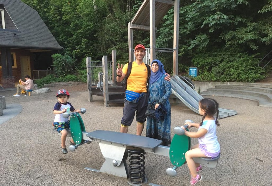 caption: Mariam Khazal's parents Mohammed Khazal and Rasha Ibrahim pose for a photo at a Seattle park while Mariam's little sister and a friend play on the seesaw, summer 2019.