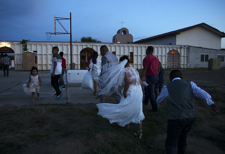 caption: Rosio Lopez leaves the mass wedding ceremony with her newlywed husband Alejandro Cruz at the end of the night after they were married along with 22 other couples on Sunday, June 2, 2019, at Our Lady of the Desert Church in Mattawa.