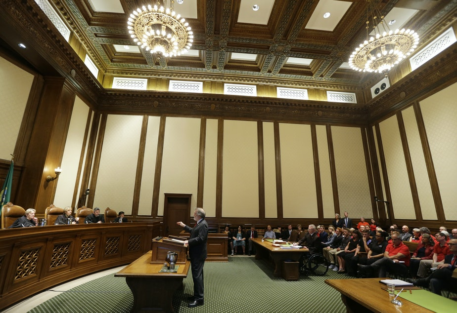 caption: Alan Copsey, center, a deputy attorney general for the state of Washington, speaks during a hearing before the Washington State Supreme Court regarding a lawsuit against the state over education funding, Wednesday, Sept. 7, 2016, in Olympia, Wash.