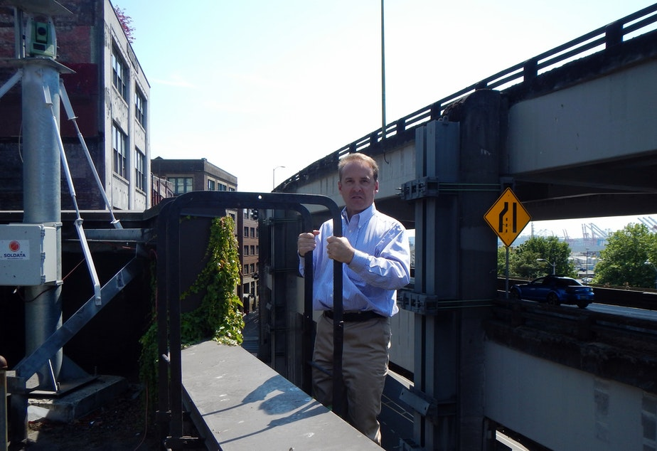 Architect Brian Runberg climbing onto the roof of the building he owns, with a building motion detector above him and the Alaskan Way Viaduct directly behind him.