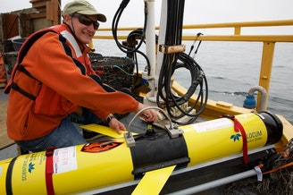 OSU oceanographer Jack Barth prepares a glider that will spend weeks flying through the ocean, collecting data on ocean acidification and oxygen levels. CREDIT: KRISTIAN FODEN-VENCIL