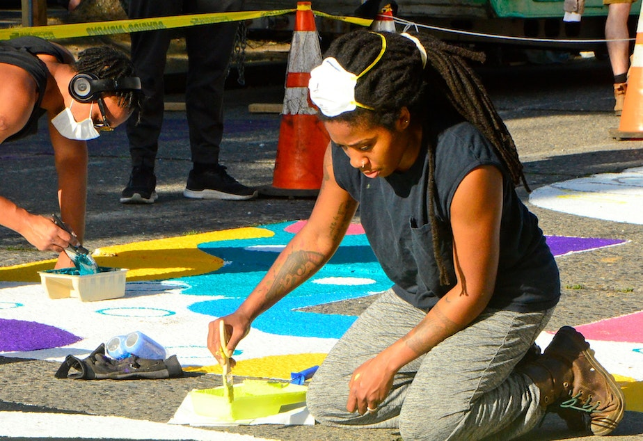 caption: Artist Aramis O. Hamer at work on the Black Lives Matter mural in the CHOP in Seattle.