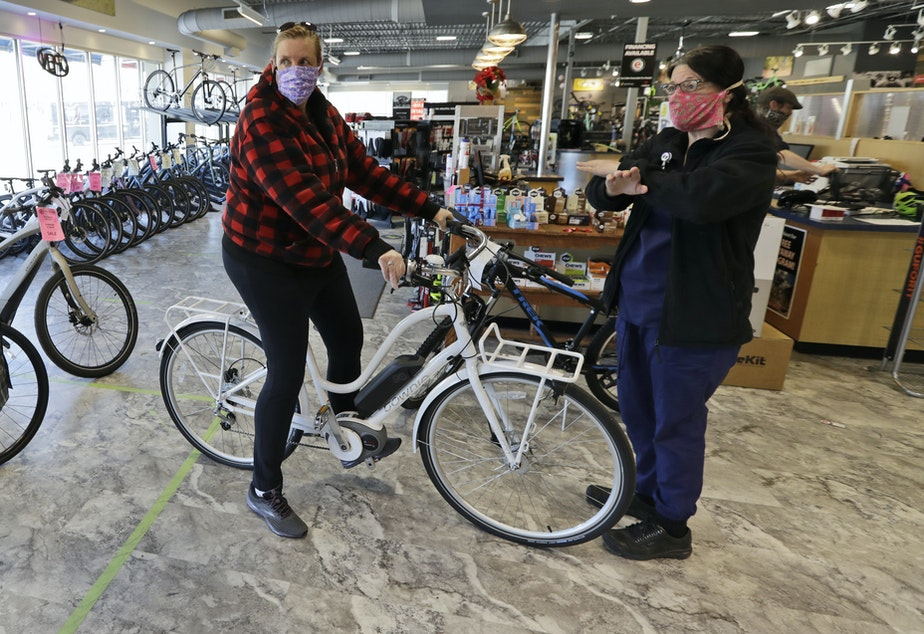 caption: Store manager Josh Hayden, left to right, talks with Kay Amey and Jackie Gee about a new bicycle at Eddy's Bike Shop on Tuesday in Willoughby Hills, Ohio. Bike shops in most states were exempt from shutdown orders and sales have been up.