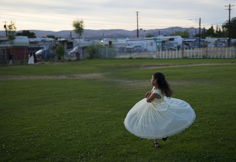 caption: Esmeralda Rosas, 5, twirls in circles outside of a mass wedding ceremony where 23 couples were married on Sunday, June 2, 2019, at Our Lady of the Desert Church in Mattawa.