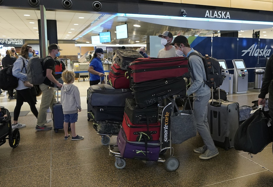 caption: Passengers wearing masks walk with luggage near an Alaska Airlines check-in area, Monday, March 1, 2021, at Seattle-Tacoma International Airport in Seattle.