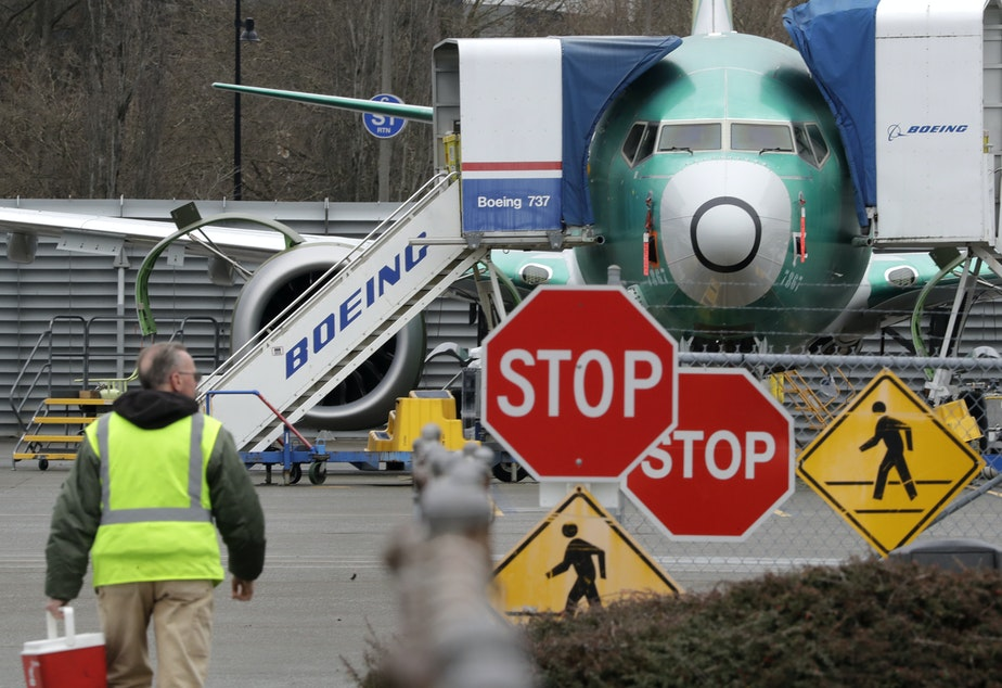 caption: A Boeing worker walks near a 737 MAX jet in Renton, Wash.