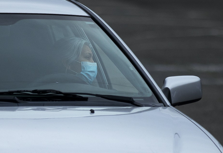 caption: Soledad Colmenares speaks to Father Jose Alvarez during walk and drive through confessions on Friday, April 24, 2020, in the parking lot at Holy Family Roman Catholic Church in White Center.