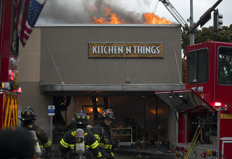 caption: Firefighters work to put out a fire at Kitchen 'N Things on Monday, October 7, 2019, at the intersection of NW Market Street and 24th Avenue Northwest in Seattle.