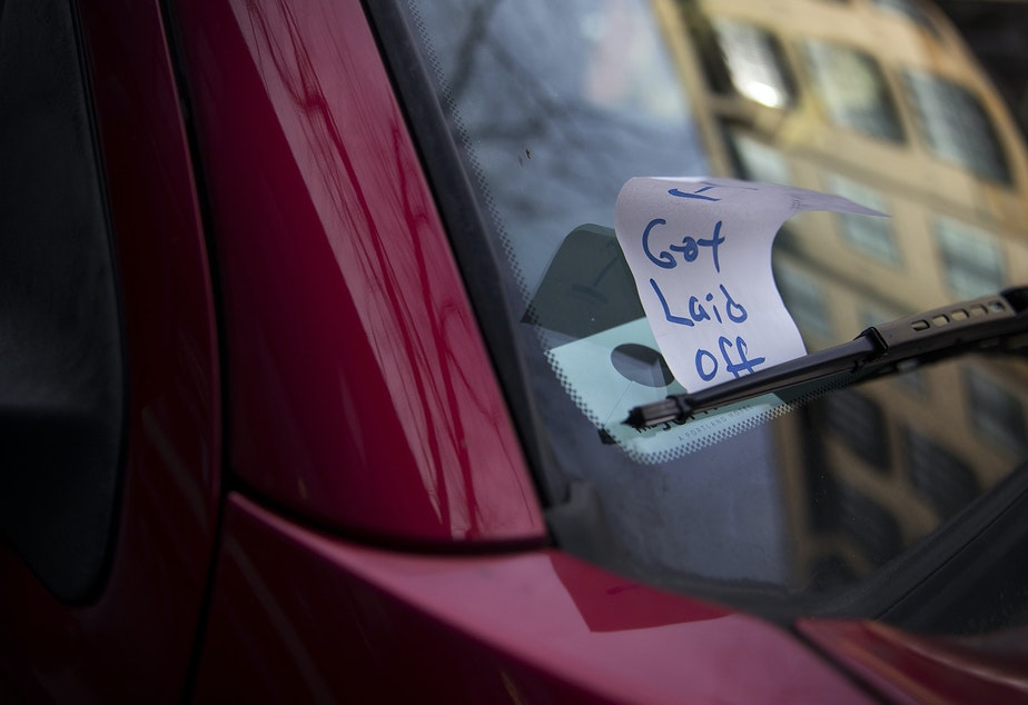 caption: A piece of paper meant to look like a previously issued parking ticket is shown under the windshield wiper of a vehicle with a handwritten note reading 'I got laid off,' on Tuesday, March 17, 2020, on Ballard Avenue Northwest in Seattle.