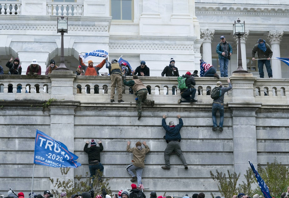 caption: Supporters of President Donald Trump climb the west wall of the the U.S. Capitol on Jan. 6.