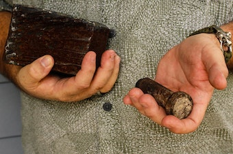 Joe Dittmar holds remnants of the World Trade Center — a section from one of the core beams of the South Tower, right, and a bolt from a steel beam.