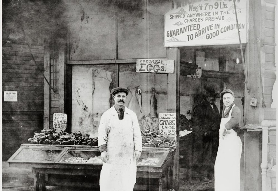 caption: Solomon Calvo (left) and Fred August in front of the Waterfront Fish and Oyster Co., Pike Place Market, Seattle, ca. 1918. Calvo was one of the original Sephardic migrants to Seattle.