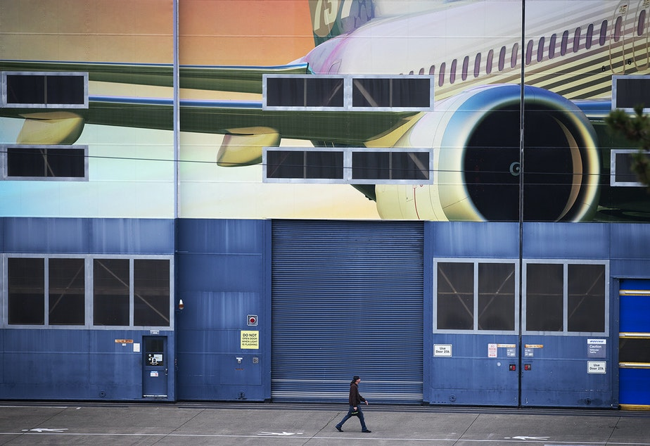 caption: A Boeing employee walks out of the Boeing Renton Factory after shift change on Monday, December 16, 2019, in Renton.