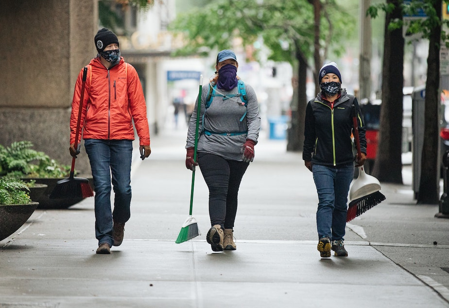 caption: People in downtown Seattle on Sunday, May 31, 2020, arrive with their own cleaning supplies to help tidy the city up again after a night of protests against racialized police violence. The protests were tied to the death of George Floyd, a Black man, at the hands of police.