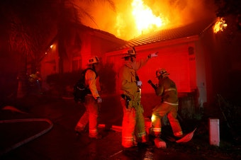 Firefighters try to beat the Woolsey Fire in the early hours Friday. One day earlier, the blaze ignited as mourning residents tried to cope with quite another kind of terror in Thousand Oaks, Calif.