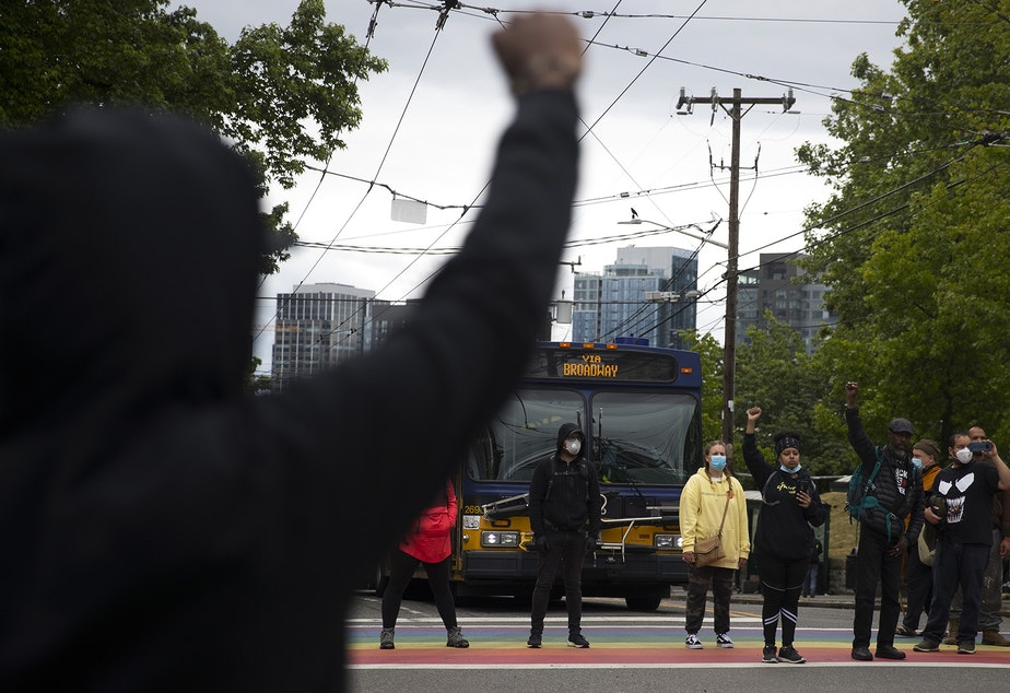 caption: Protesters form a circle and block traffic at the intersection of Broadway and East Pine Street after the Seattle Police Department cleared the Capitol Hill Organized Protest zone, CHOP, early Wednesday, July 1, 2020, in Seattle.