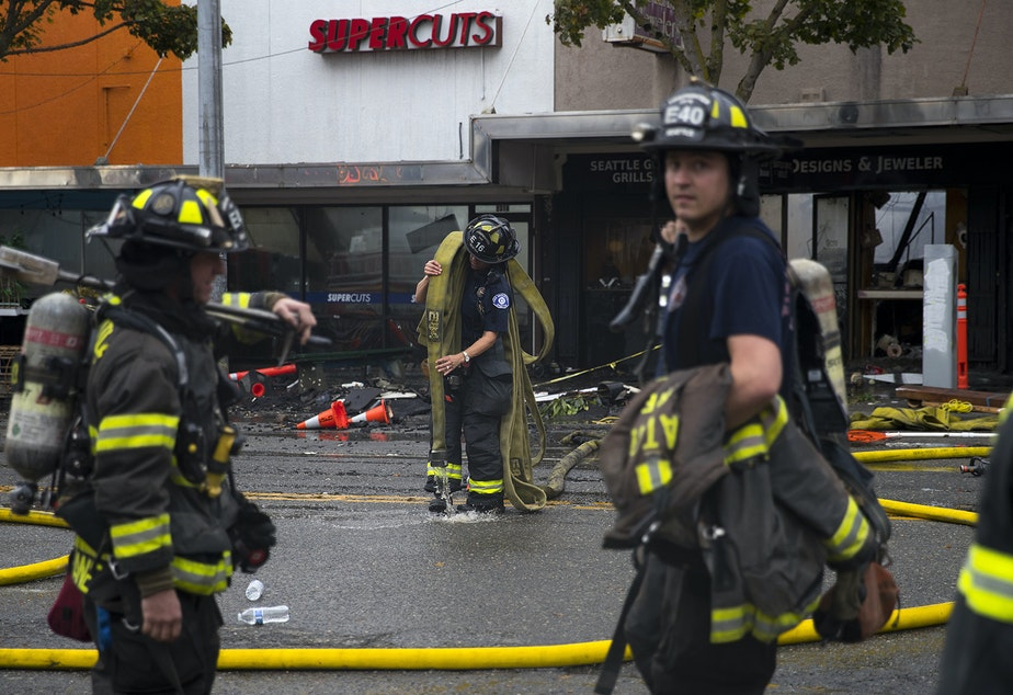 caption: Firefighters work to put out a fire on Monday, October 7, 2019, at the intersection of NW Market Street and 24th Avenue Northwest in Seattle.