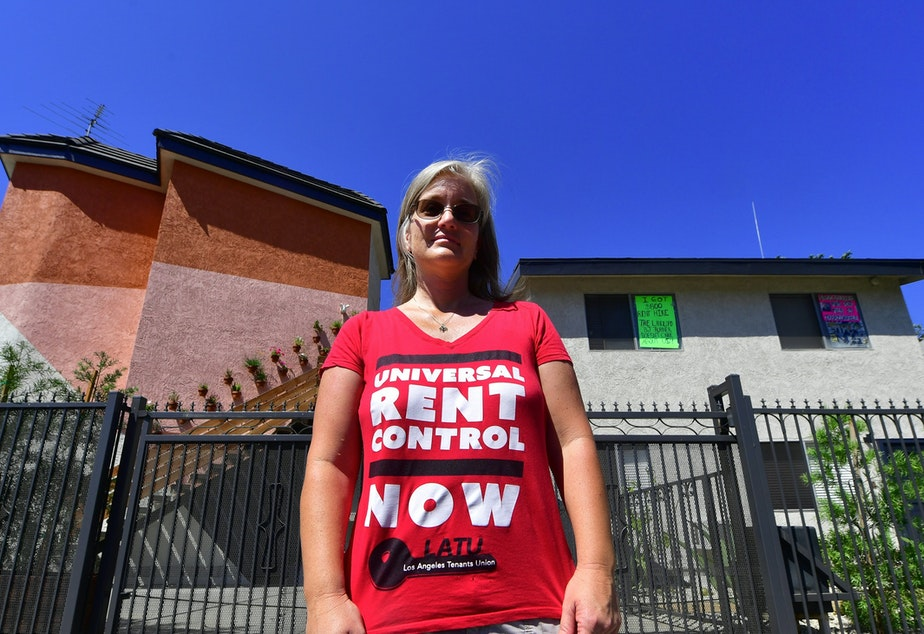 Community activist Elizabeth Blaney stands in front of the apartment block where, with no rent control due to the year it was built, the landlord has increased some rentals by as much as $800.