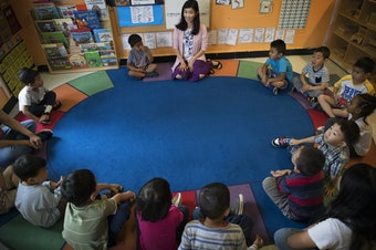 Seattle Preschool Program teacher Hien Do, center, sits in a circle with her students on Wednesday, June 28, 2017, at the ReWA Early Learning Center at Beacon, in Seattle.