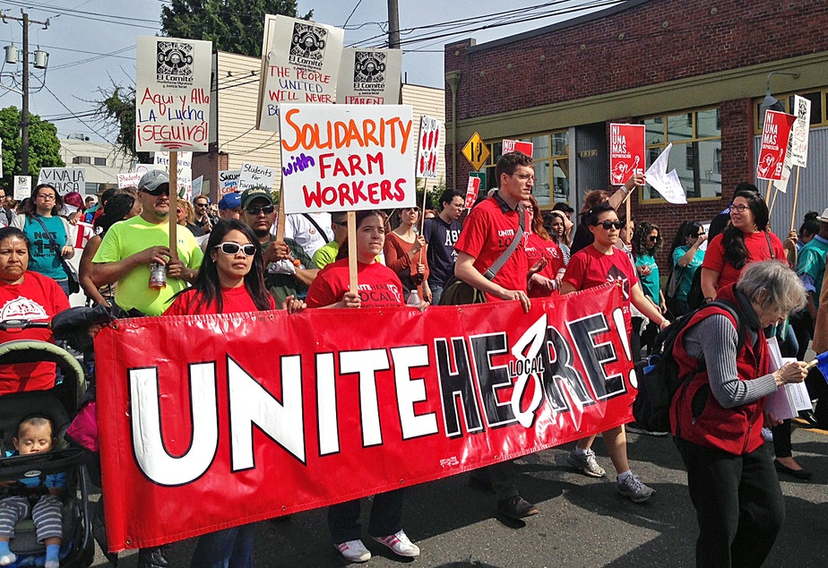 caption: People walk in the May Day labor march in Seattle on Friday, May 1, 2015.