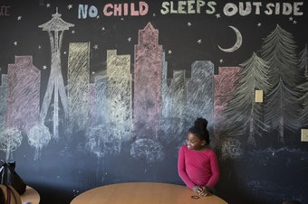 Mariah Hicks, 7, stands in front of a chalk drawing depicting downtown Seattle in a common area at Mary's Place, a homeless shelter.