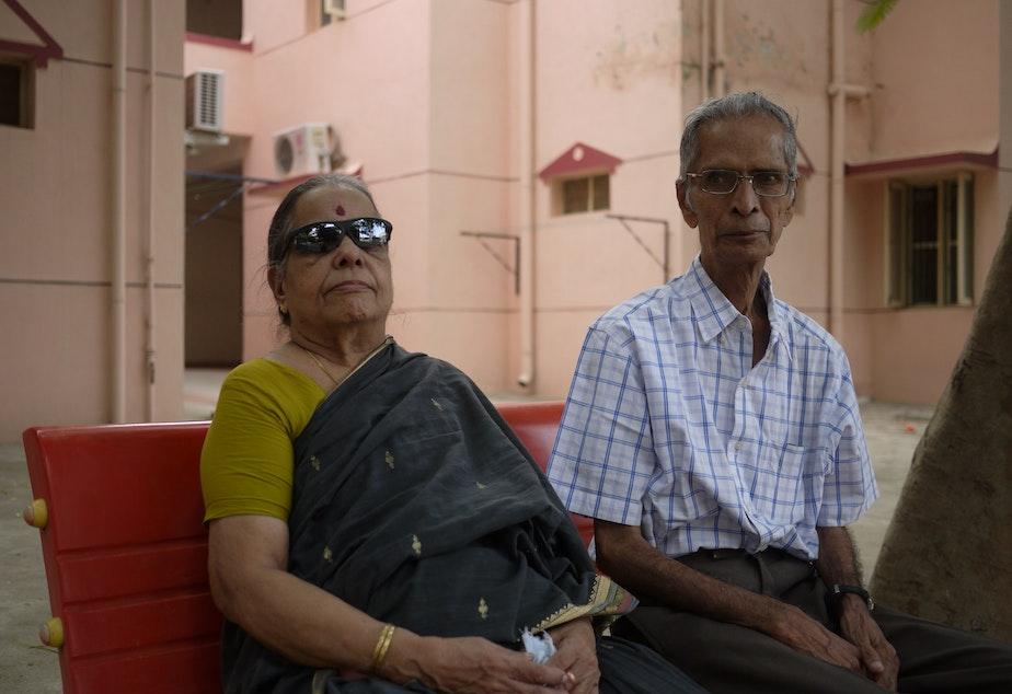 caption: Mahadevan Iyer and a friend sit outside his apartment at a senior living community near Chennai, India.