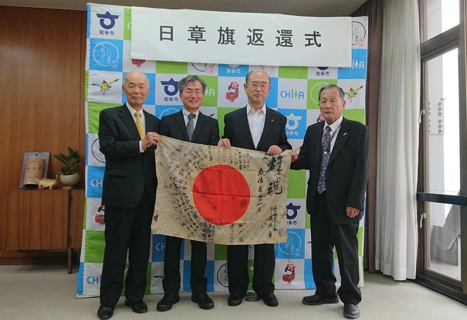 caption: The WWII flag submitted by Greg Murphy of Portland was traced back to a fallen Japanese soldier who carried it into battle in 1944. The mayor of Chita City, Japan, second from right, hosted a ceremony in 2019 where a nephew of the soldier, second from left, accepted the returned flag.